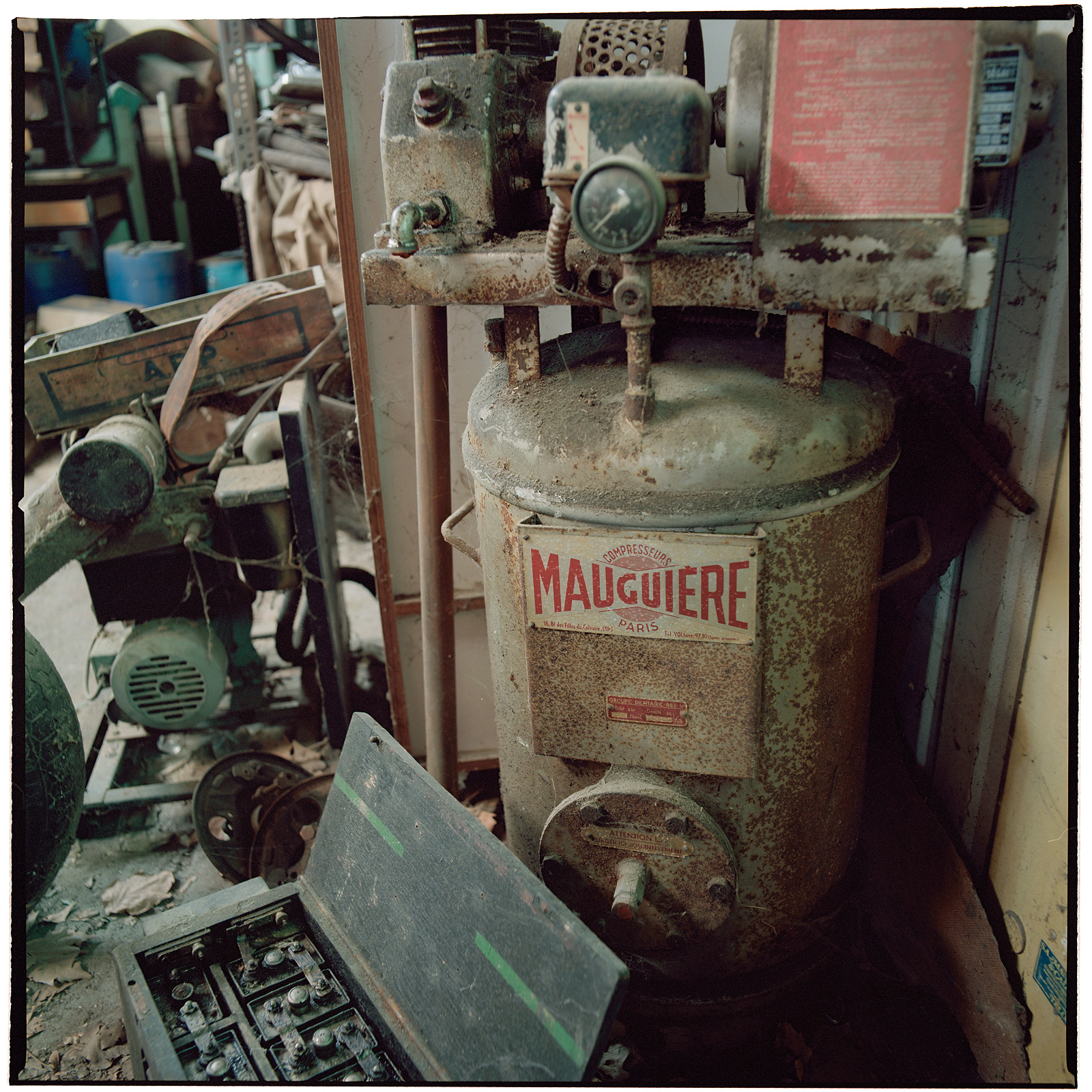 Maugiére compressor and an old battery in the workshop area at Cimetière camions de pompiers, France.