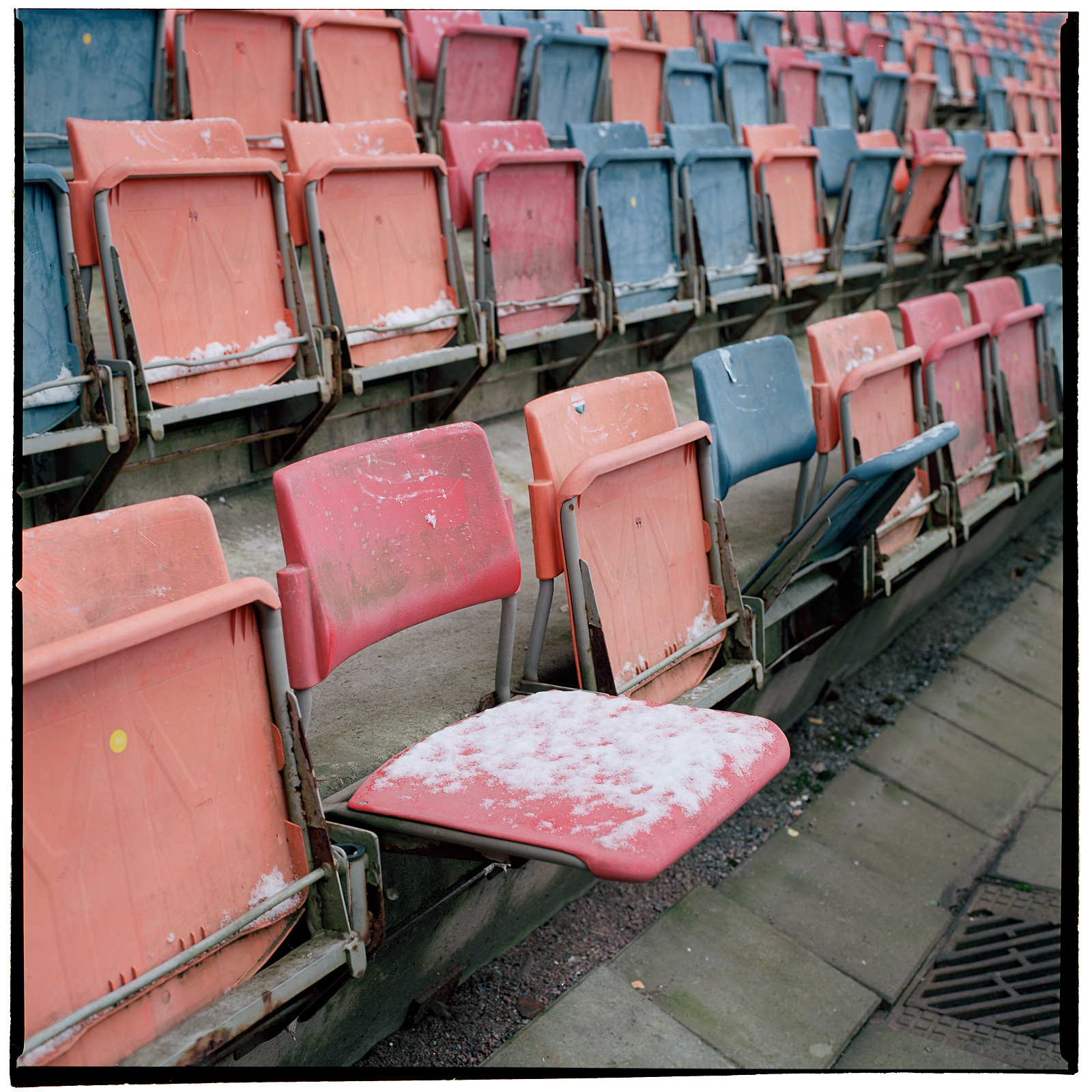 The season's first snow settled on worn seats at Råsundastadion. Solna, Stockholm, Sweden. October 2012.